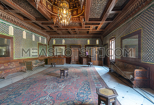 Manial Palace of Prince Mohammed Ali. Moroccan hall at the ceremonies building with blue Turkish floral pattern ceramic tiles, vintage furniture, and framed mirrors, Cairo, Egypt