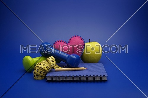 Fitness and weight loss concept with dumbbells, measuring tape, heart, green apple and new notebook on blue background