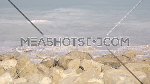 Slow pan of salt covered rocks on the shore of the Dead Sea