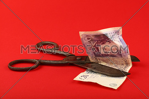UK and Great Britain financial crisis, decline of British economy and pound illustrated, old vintage scissors cut twenty pounds banknote over red