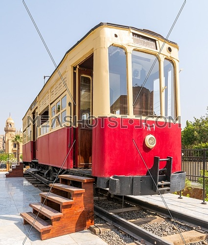 Exterior of vintage tram with wooden stairs near open doors located on rails on sunny day on town street