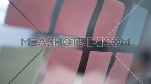 colorful memo stickers on  glass wall window,  modern office meeting room blurred in background