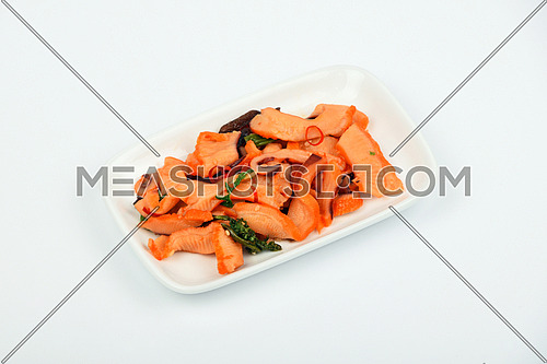 Seafood calamari squid, seaweeds and chili marinated salad snack with souse on white dish plate over white background, high angle view