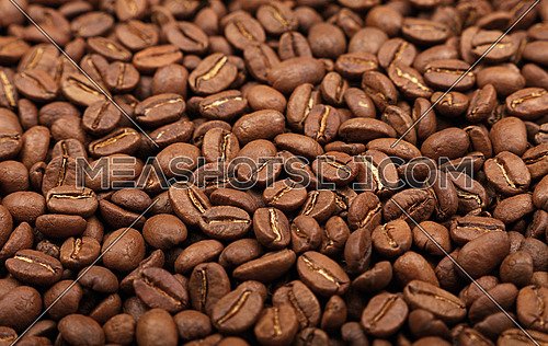 Roasted brown Arabica coffee big beans background pattern, close up, high angle view