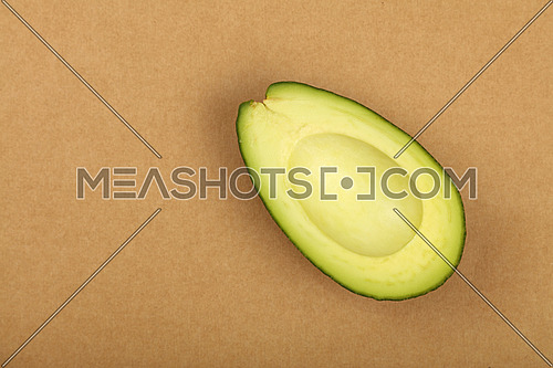 One fresh ripe green avocado half without pit stone on natural brown kraft paper parchment background, detail, close up, elevated top view