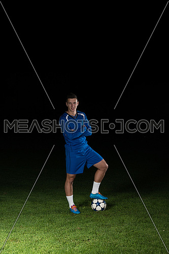 Portrait Of A Soccer Player And Ball On Football Stadium Field Isolated On Black Background