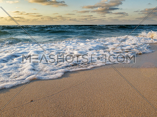 Sea waves breaking on a sandy beach with clouds in the background