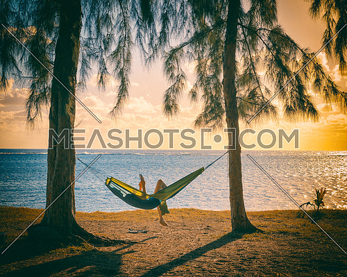 Silhouette of woman reading in hammock,used split toning effect.