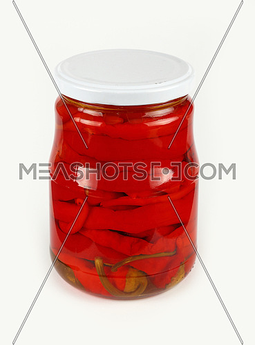 Close up of one glass jar of pickled red hot cherry chili pepperoncini peppers over white background, high angle view
