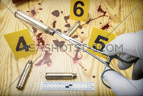 scene of crime, Scientific police picking up bullet cap with tweezers, rule of ballistic measurement, conceptual image, horizontal composition