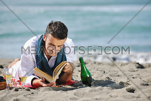 young man relaxing on beach at beautiful sunny day while reading book representing summer school and education concept