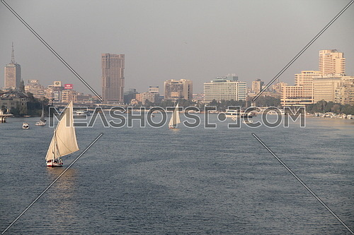 a photo for Cairo and river Nile from one of the bridges showing boats sailing , hotels and buildings