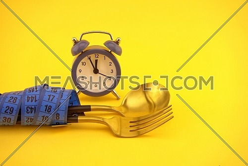Golden cutlery wrapped with measuring tape near alarm clock on yellow background, weight loss or diet concept with copy space