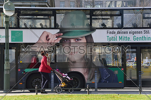 a woman pushing a baby stroller in the streets of berlin