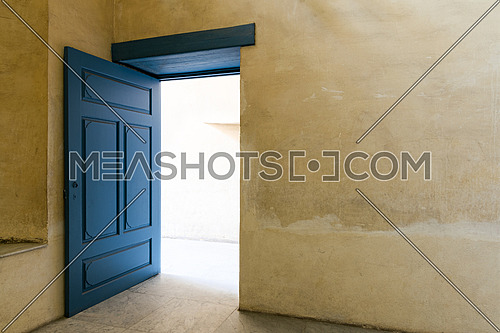 Blue wooden vintage door at an old historic building with plaster wall, Medieval Cairo, Egypt