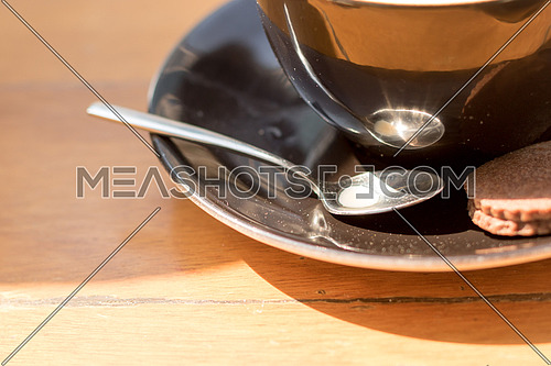 black cup and its plate and spoon