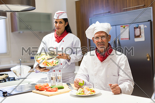 older middle eastern chef and his assistant enjoy preparing meals in the kitchen