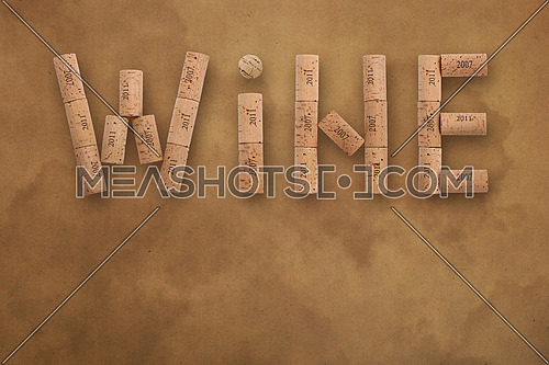 Word WINE shaped by natural wooden wine bottle corks of different vintage years over background of brown paper parchment