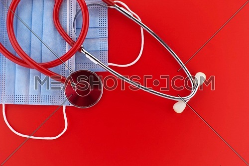 Face mask and stethoscope over a red background with copyspace for text