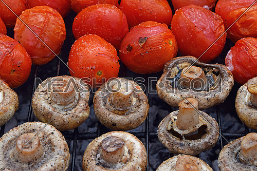 Vegetables in salt and spices being cooked on char grill, white champignons portobello mushrooms and red small tomatoes