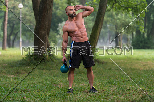 Muscular Adult Caucasian Man Doing A Exercise Outdoors With Kettlebell