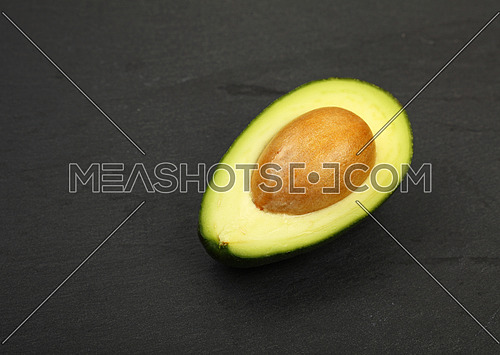 One fresh ripe green avocado half with pit stone on black slate board background, detail, close up, high angle view