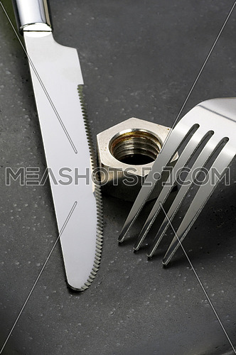 hex nut on a black plate with knife and fork