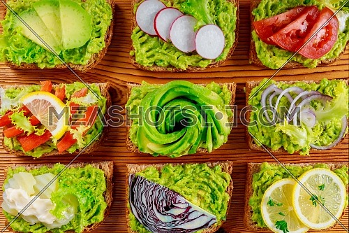 Fresh healthy vegetarian breakfast with wholegrain sandwiches, avocado toasts with different toppings