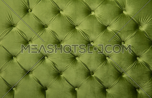 Green velvet capitone textile background, retro Chesterfield style checkered soft tufted fabric furniture diamond pattern decoration with buttons, close up