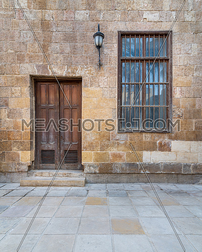 Facade of old abandoned stone bricks wall with wooden door and window covered with wrought iron bars and antique lantern, Cairo, Egypt
