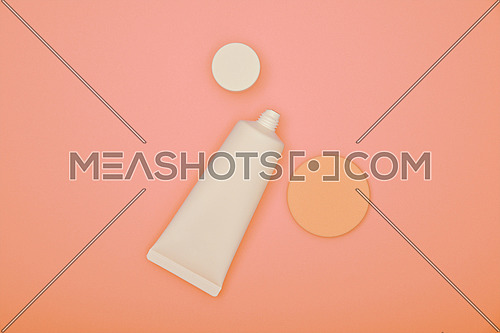 Close up one white tube of makeup foundation cream and beige sponge over peachy pink background, elevated top view, directly above