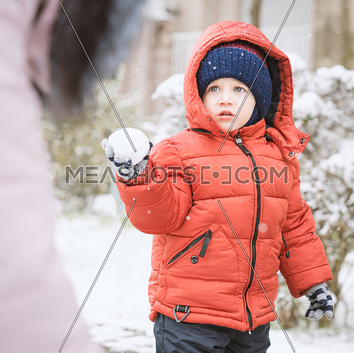 Child while it snows looks towards the mother with a snowball in his hands