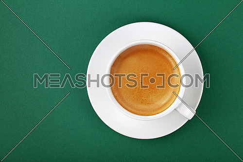 Close up one full white cup of espresso coffee on saucer on green table background, elevated top view, directly above