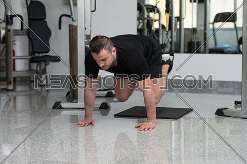 Attractive Young Man Does Crossfit Push Ups With Trx Fitness Straps In The Gym's Studio