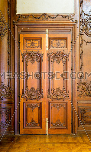 Closed elegant lumber door with engraved decorations, installed in wooden ornamental archway leading to old building