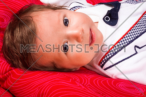 Image of cute newborn boy smiling, closeup portrait of adorable child  on red background.