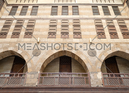 Facade of caravansary (Wikala) of al-Ghuri with vaulted arcades, wooden balustrades, windows with interleaved wooden grids (mashrabiya), Cairo, Egypt