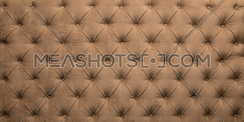 Brown beige velvet capitone textile background, retro Chesterfield style checkered soft tufted fabric furniture diamond pattern decoration with buttons, close up