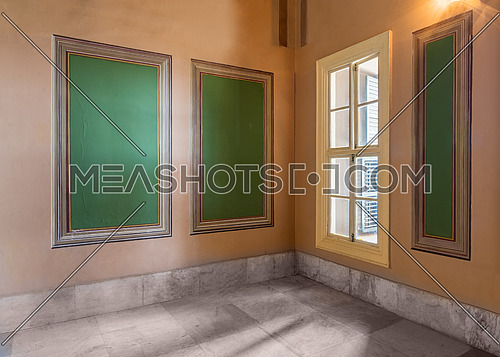 Three beautiful elegant rectangular green frames with ornate border and wooden window with green shutters on orange wall with white marble floor, in abandoned old building