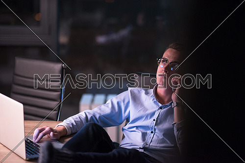 Young businessman using mobile phone while working on laptop at night in dark office.