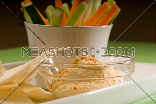 middle eastern hummus dip on a glass bowl with homemade pita bread and raw vegetable