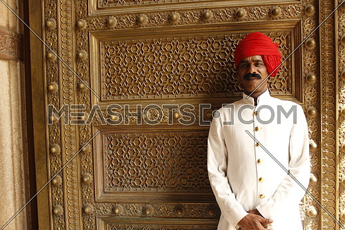 An indian man wearing a red turban standing by a golden door