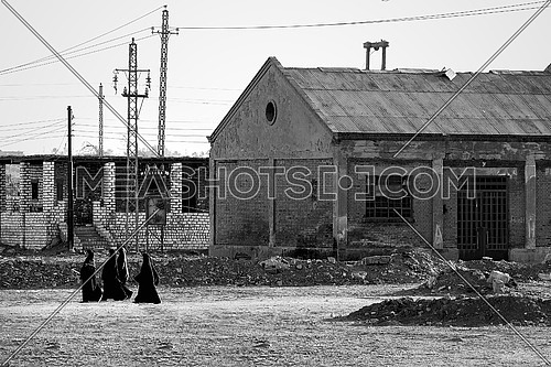 a black and white image of an abandoned house and four women walking in black veil
