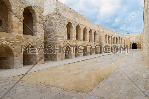 Aged building of stone blocks with archs and windows on cloudy day