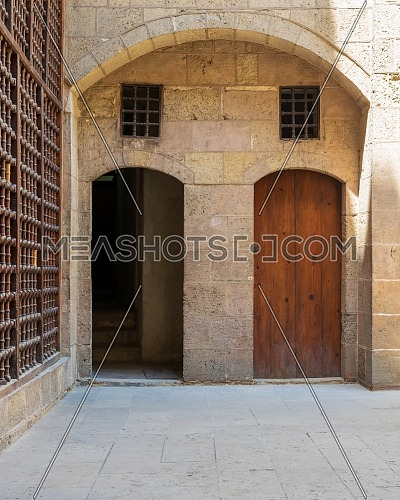 Exterior brick stone passage with two adjacent vaulted opened and closed wooden grunge doors leading to Beit El Sehemy Historical building, Moez Street, Old Cairo, Egypt
