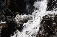 Waterfall fast stream, rapid water with drops over the rocks and stones in watercourse of river or brook