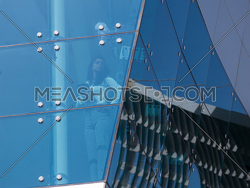 young business woman talking  on mobile phone  at modern office building outdoor shoot with blue sky in background