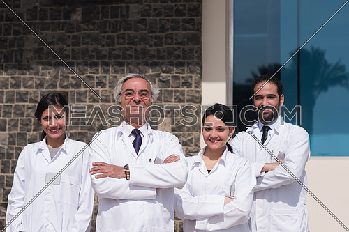 portrait of middle eastern team doctors in front of a large modern hospital