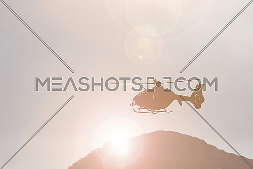 Mountain rescue helicopter against the sun in the mountains
