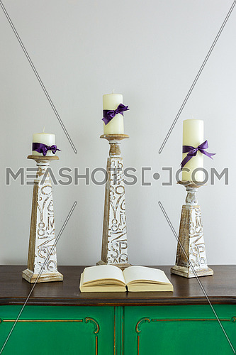 Three wooden candlesticks with engraved inscriptions holding three candles and opened old book with blank pages on green vintage wooden sideboard